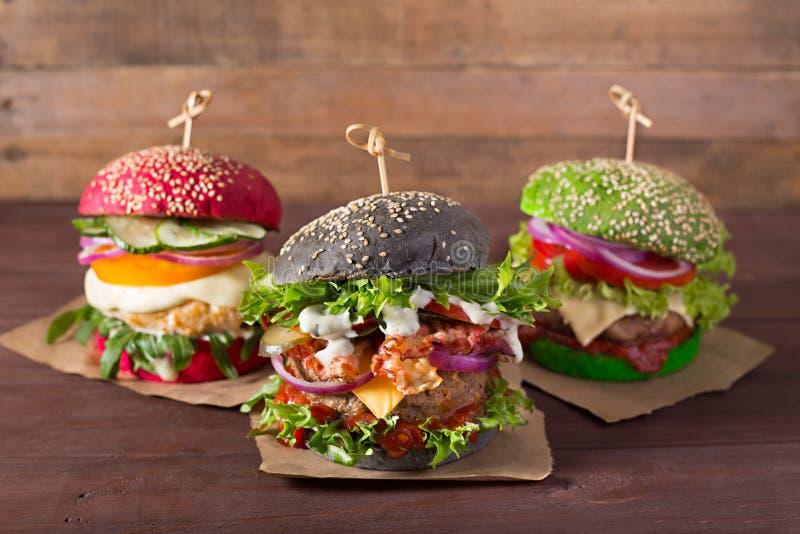 Czerni, zielenieje, czerwoni hamburgery na drewnianym tle zdjęcie stock