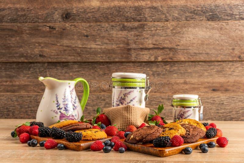 Czernicy, czarne jagody, malinki, fundy i biali gliniani naczynia, fotografia royalty free