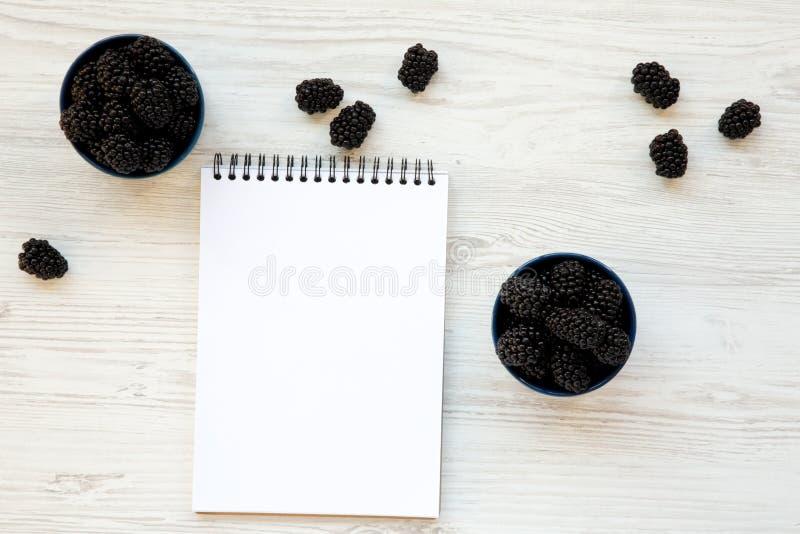 Czernicy w ceramicznych błękitnych pucharach z notepad Lato jagoda Od above, koszt stały, odgórny widok zdjęcie royalty free