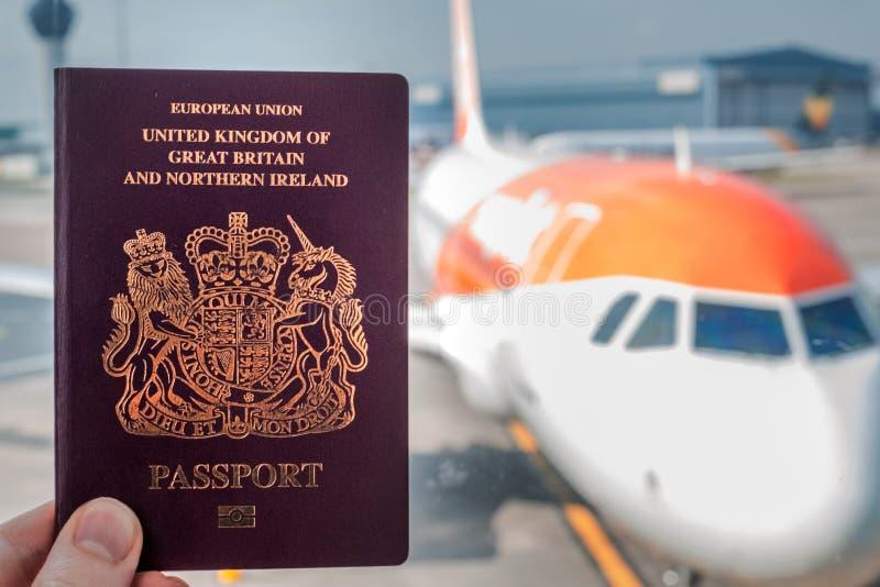 Czerwień Brytyjski paszport podtrzymujący przeciw tłu rodzajowy samolot na jaskrawym słonecznym dniu zdjęcia stock