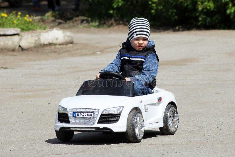 Czerwiec 2, 2018 Izhevsk, Rosja Chłopiec jeżdżenia zabawki samochód na ruchu drogowego boisku zdjęcia royalty free
