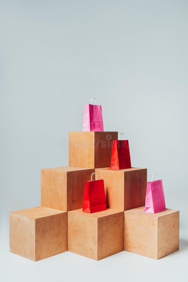 czerwieni i menchii torby na zakupy na drewnianych sześcianach, lato zdjęcia stock