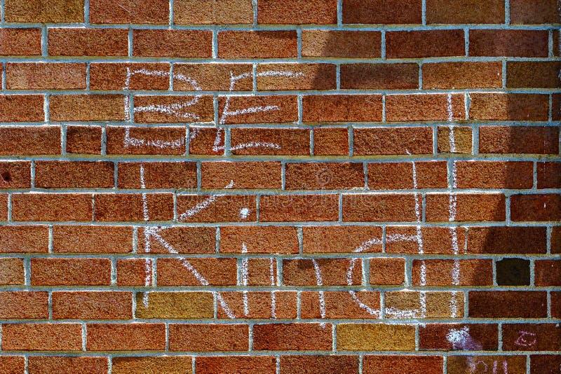 Czerwona ściana z cegieł kredy inskrypcja Był Miła i chorągwiana usa fotografia royalty free