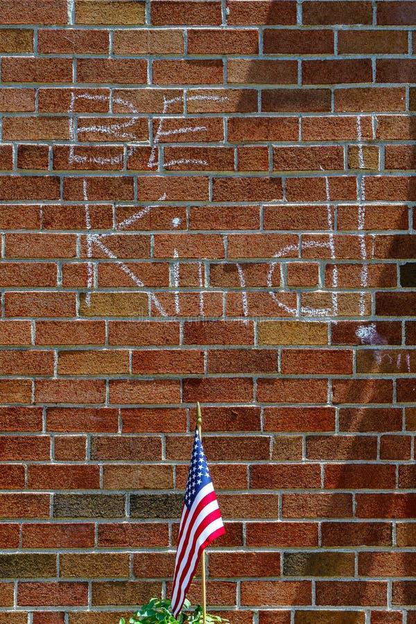 Czerwona ściana z cegieł kredy inskrypcja Był Miła i chorągwiana usa obraz stock