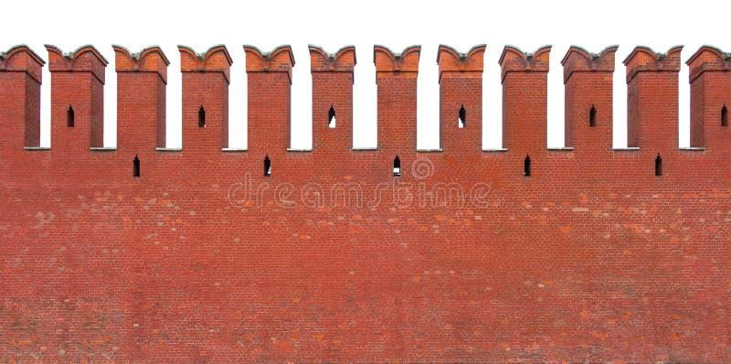 Czerwona ściana z cegieł z merlon, odizolowywającym na białym tle zdjęcie stock
