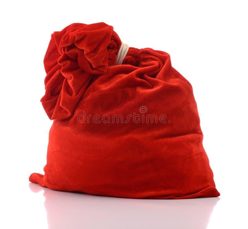 Czerwona Święty Mikołaj torba folował na biały tle, fotografia royalty free