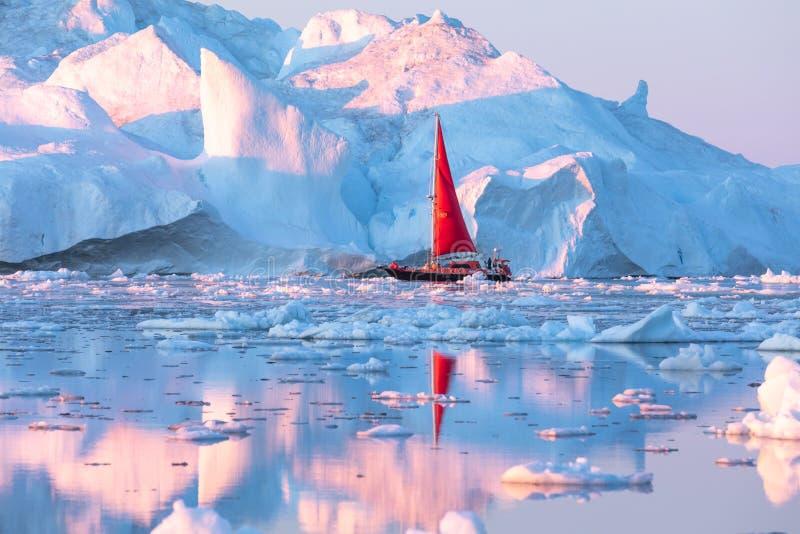 Czerwona żaglówka pływa statkiem wśród gór lodowych zdjęcia royalty free