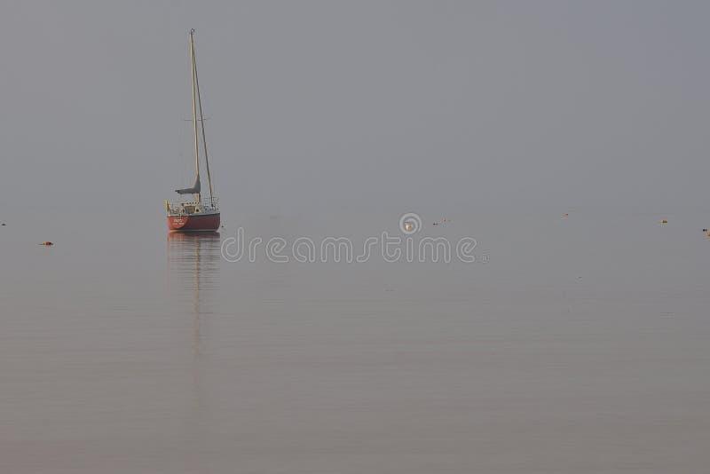 Czerwona żaglówka siedzi w zatoczce w mgle zdjęcia stock