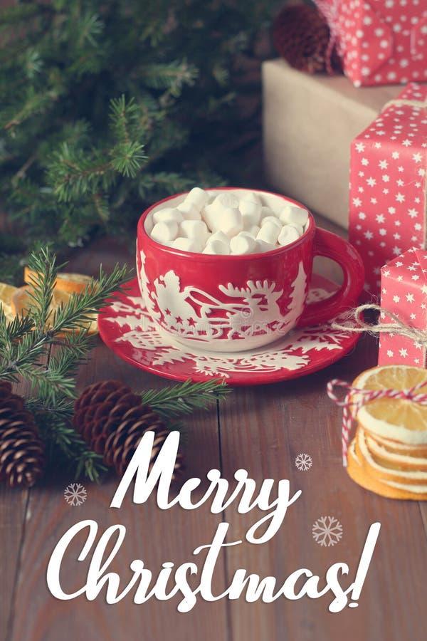 Czerwona Bożenarodzeniowa filiżanka z gorącym kakao i marshmallows na drewnianym stole obraz royalty free