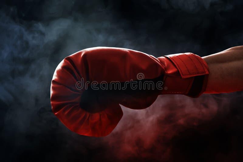 Czerwona bokserska rękawiczka na dymnych tło obraz stock