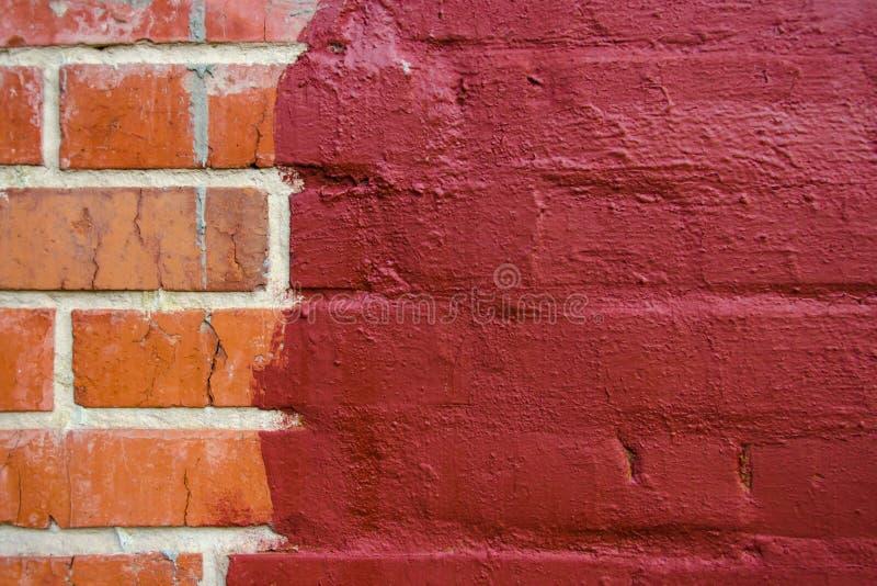 Czerwona brickwork połówka malująca w zmroku - czerwona farba zdjęcia stock
