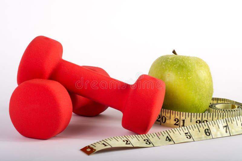 Czerwona dumbbell sprawność fizyczna, pomiarowa taśma i zieleni jabłko odizolowywająca na białym tle, fotografia royalty free