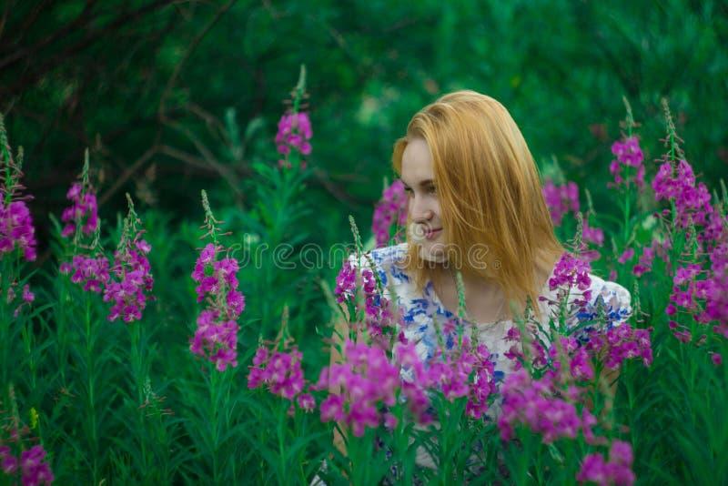 Czerwona dziewczyny pozycja na kwiat łące obraz royalty free