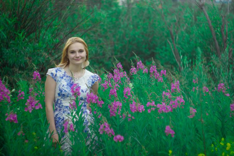 Czerwona dziewczyny pozycja na kwiat łące zdjęcia stock