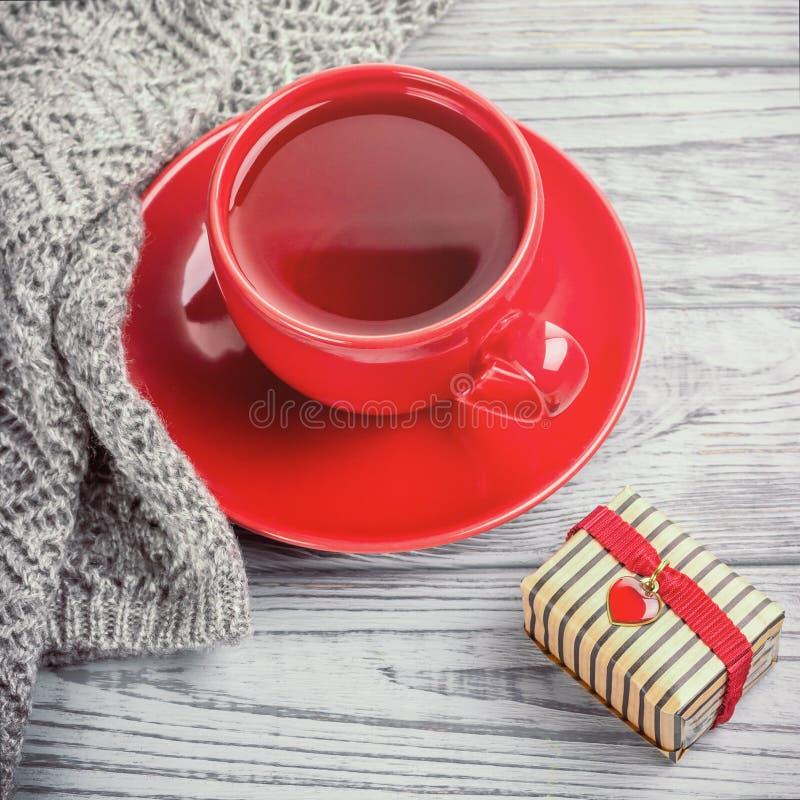 Czerwona filiżanka herbata, trykotowe mitenki i prezent dla walentynka dnia na szarym tle, fotografia royalty free