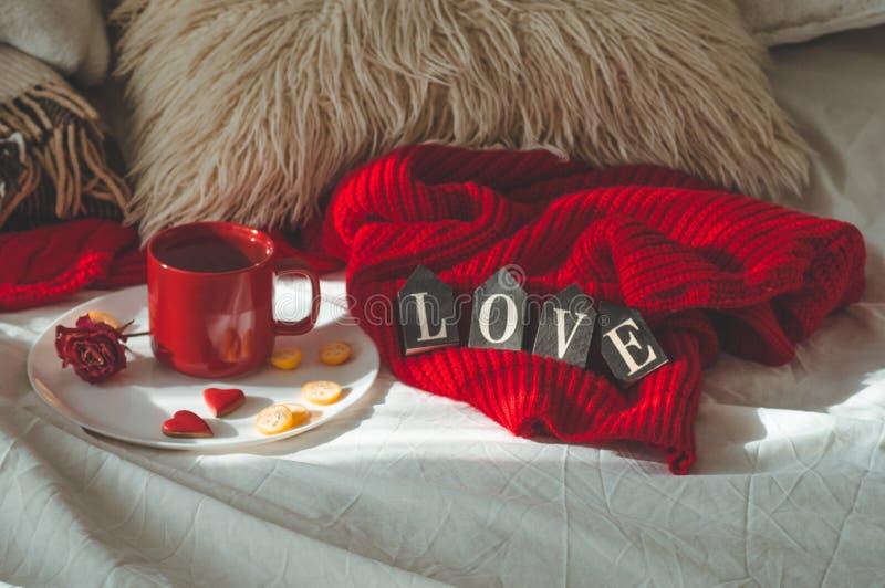 Czerwona filiżanka herbata z kumquat na talerzu i dwa serc ciastkach z słowem miłość na białym łóżku tła błękitny pudełka pojęcia zdjęcie stock