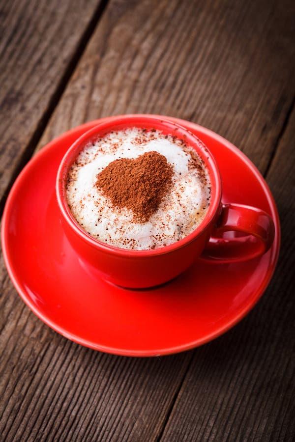 Czerwona filiżanka z cappuccino i sercem obraz stock