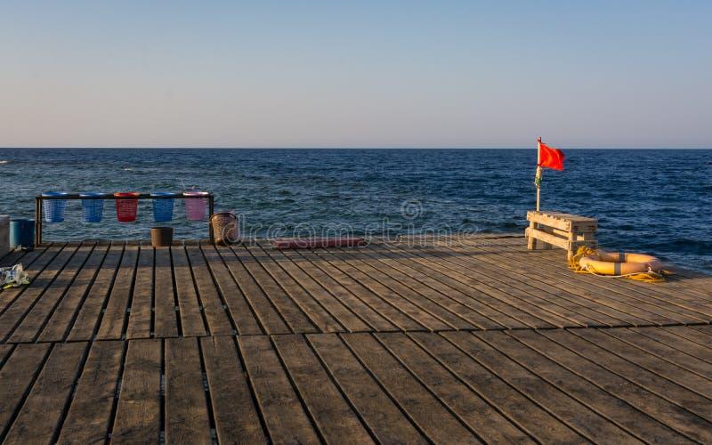 Czerwona flaga na drewnianym molu fotografia stock