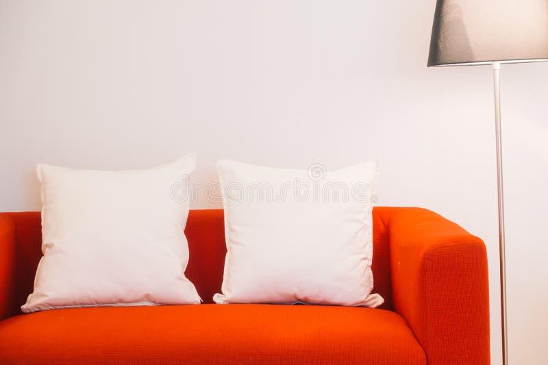 Czerwona kanapa z poduszki i światła lampą fotografia stock
