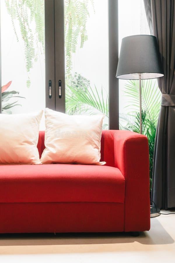 Czerwona kanapa z poduszki i światła lampą obraz stock