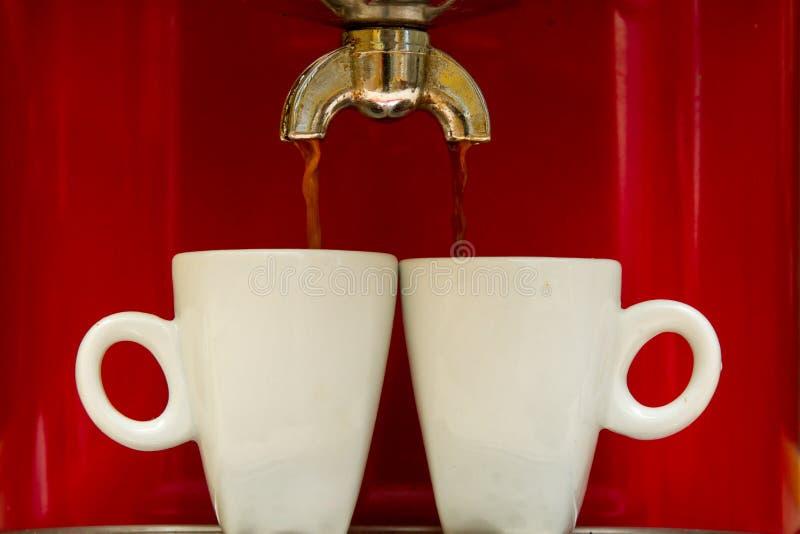 Czerwona kawy espresso maszyna nalewa kawę w dwa filiżanki zdjęcia royalty free