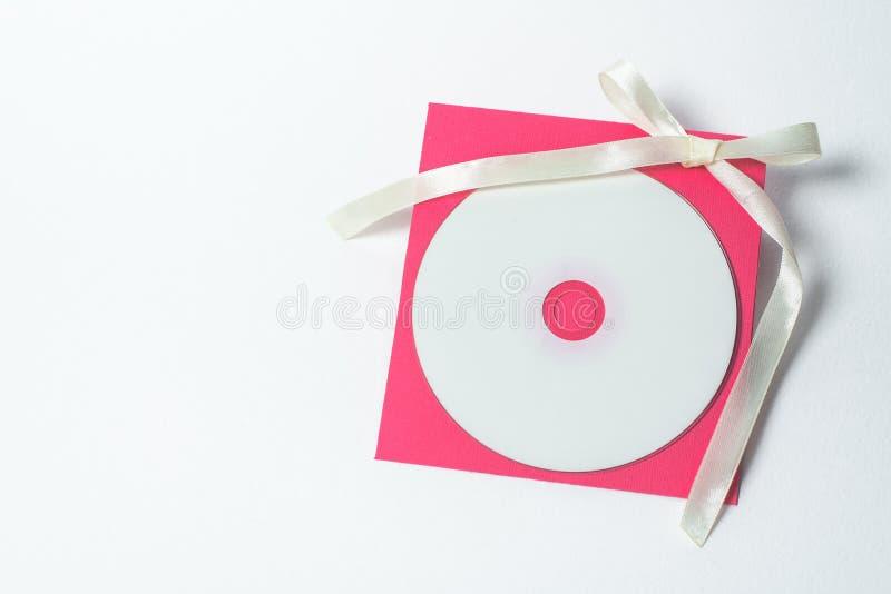 Czerwona koperta z żółtym faborkiem w formie łęku dla cd, pionowo pozycja t?a koperty kwadrata biel fotografia stock