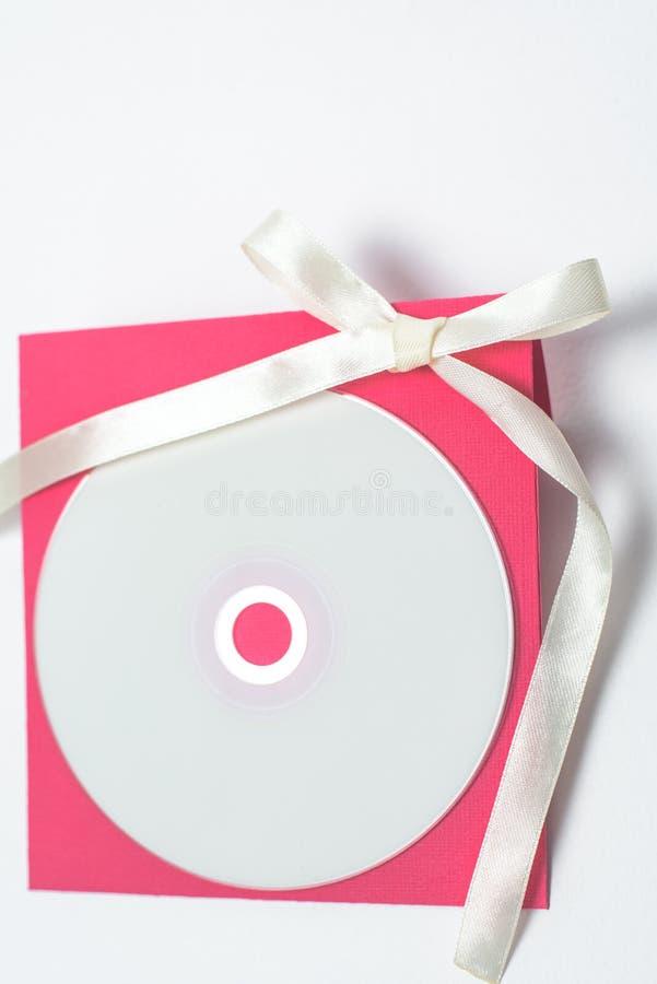 Czerwona koperta z żółtym faborkiem w formie łęku dla cd, pionowo pozycja t?a koperty kwadrata biel obrazy stock