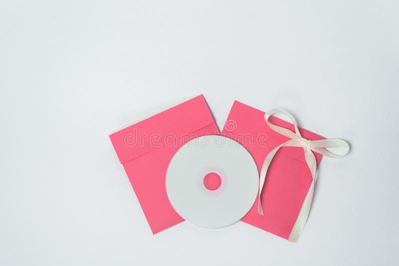 Czerwona koperta z żółtym faborkiem w formie łęku dla cd, pionowo pozycja t?a koperty kwadrata biel obraz stock