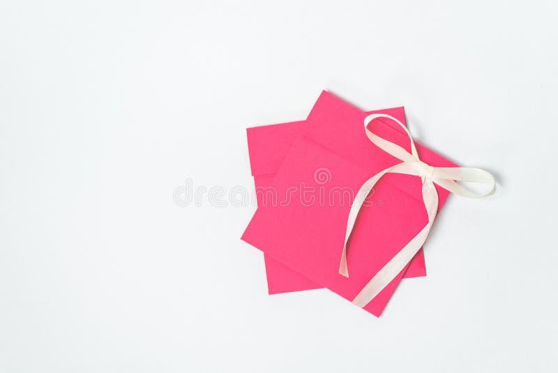 Czerwona koperta z żółtym faborkiem w formie Å'Ä™ku dla cd, pionowo pozycja t?a koperty kwadrata biel zdjęcia royalty free