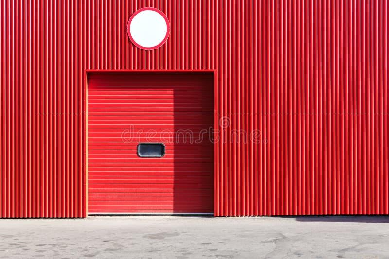 Czerwona metalu magazynu ściana z zamkniętą rolkową żaluzi bramą obrazy royalty free