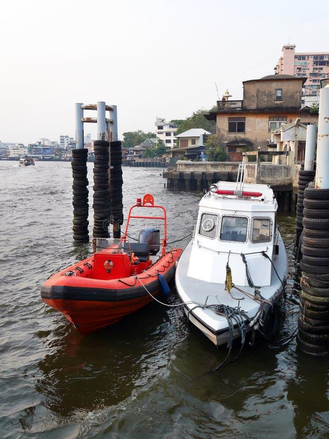 Czerwona militarna łodzi patrolowa i karetki łódź parkująca przy rzecznym portem fotografia stock