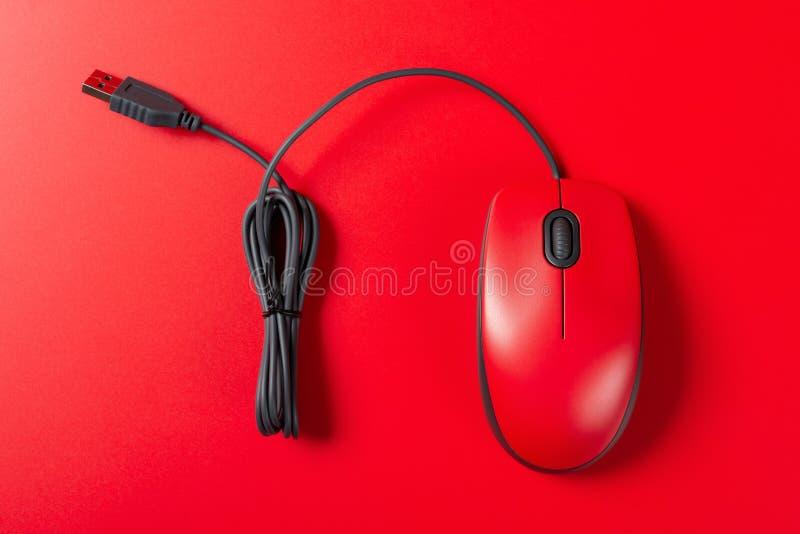 Czerwona mysz z kablem na czerwonym tle zdjęcie royalty free