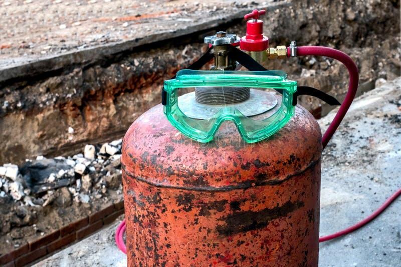 Czerwona ośniedziała benzynowej butli pozycja na bruku zdjęcie royalty free