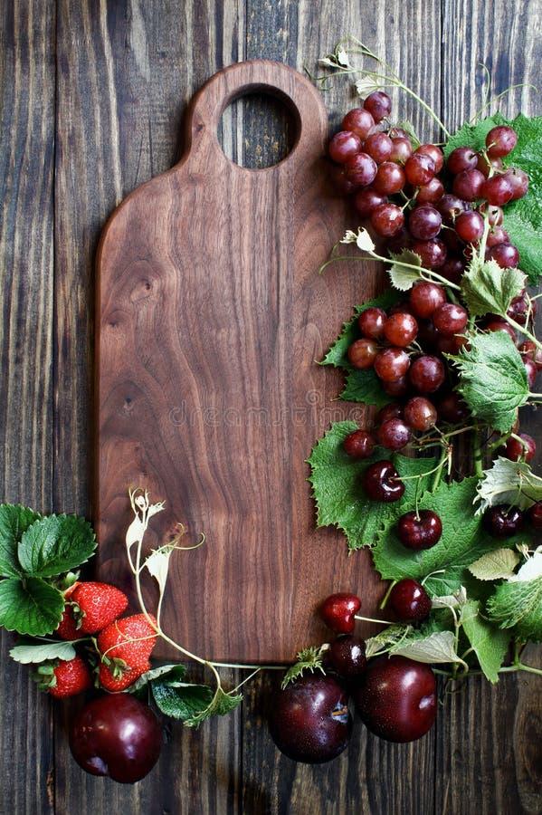 Czerwona Organicznie Wyprodukowany lokalnie owoc i Tnąca deska zdjęcie stock