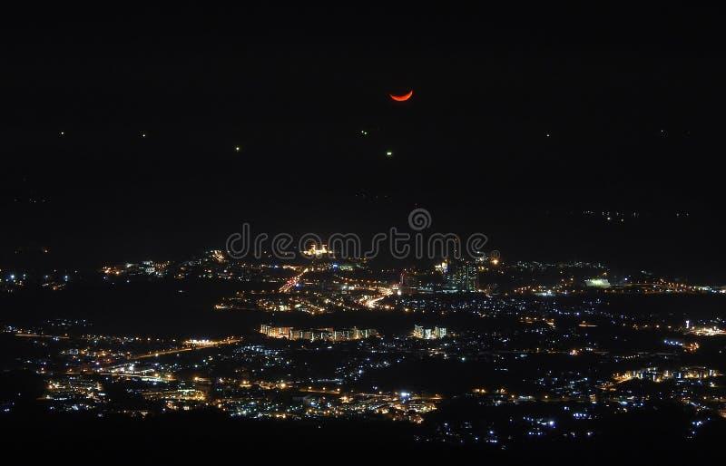 Czerwona półksiężyc nad miasta światłem zdjęcia royalty free