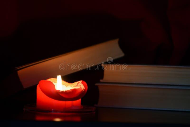Czerwona płonąca świeczka i stare książki w zmroku obraz stock