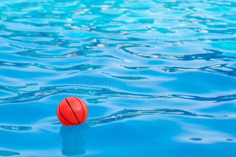 Czerwona piłka na błękitne wody pool_ obrazy royalty free