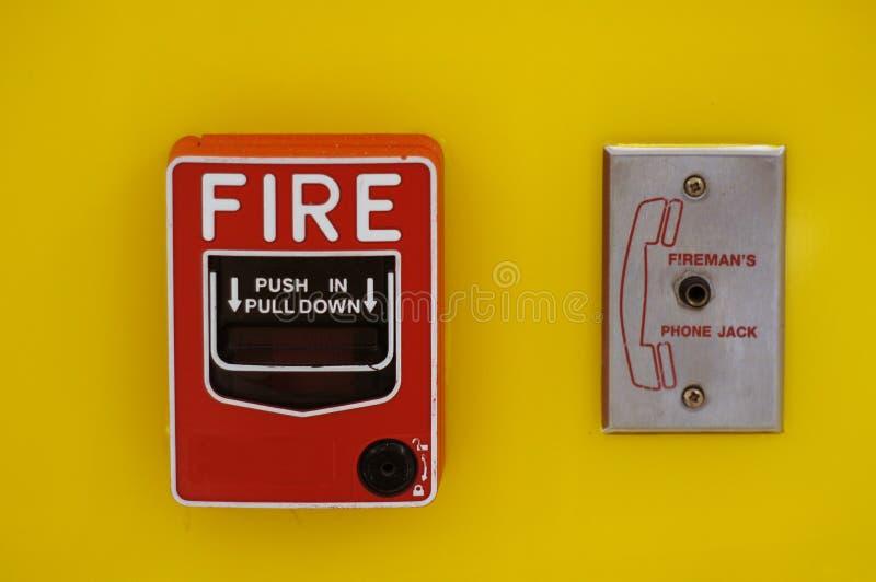 Czerwona Pożarniczego alarma ciągnienia stacji zmiana instaluje na jaskrawej kolor żółty ścianie obraz stock