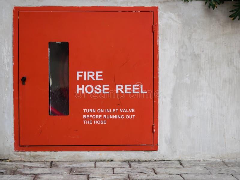 Czerwona pożarniczego węża elastycznego rolka na betonowej ścianie zdjęcia stock