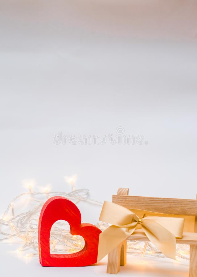 czerwona róża odizolowywa drewnianego serce z łękiem na ławce na białym tle zdjęcie royalty free