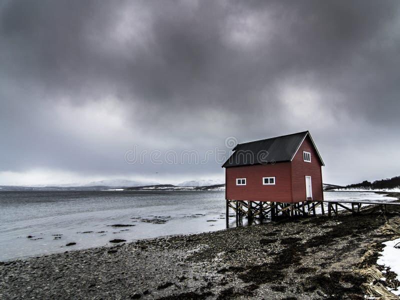 Czerwona rybak buda blisko morza w Tromso w chmurnym dniu zdjęcia stock