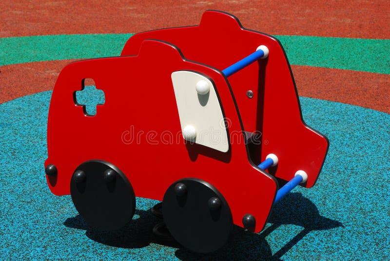 Czerwona samochodowa samochód dostawczy przejażdżka kołysa zabawkę przy boiskiem obraz stock