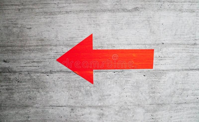 Czerwona strzała na szarej betonowej ścianie wskazuje lewica zdjęcie royalty free