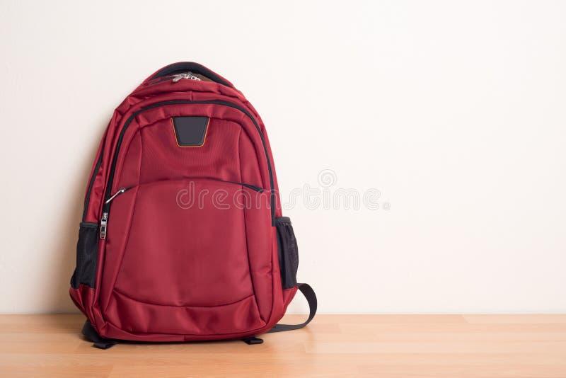Czerwona szkolna torba na drewno stole zdjęcia royalty free