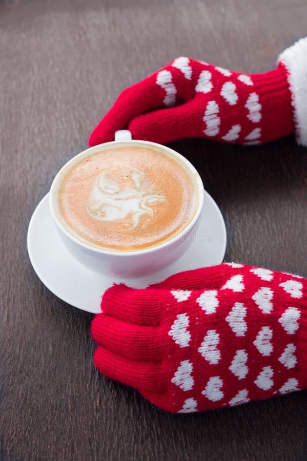 Czerwona trykotowa rękawiczek ręk chwyta filiżanka zdjęcie royalty free