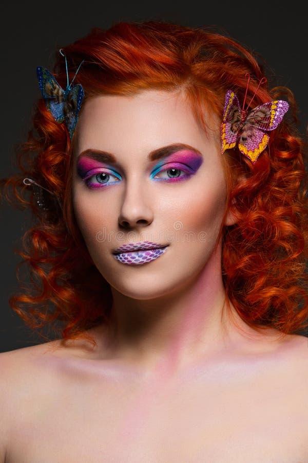 Czerwona włosiana dziewczyna z motylami fotografia stock
