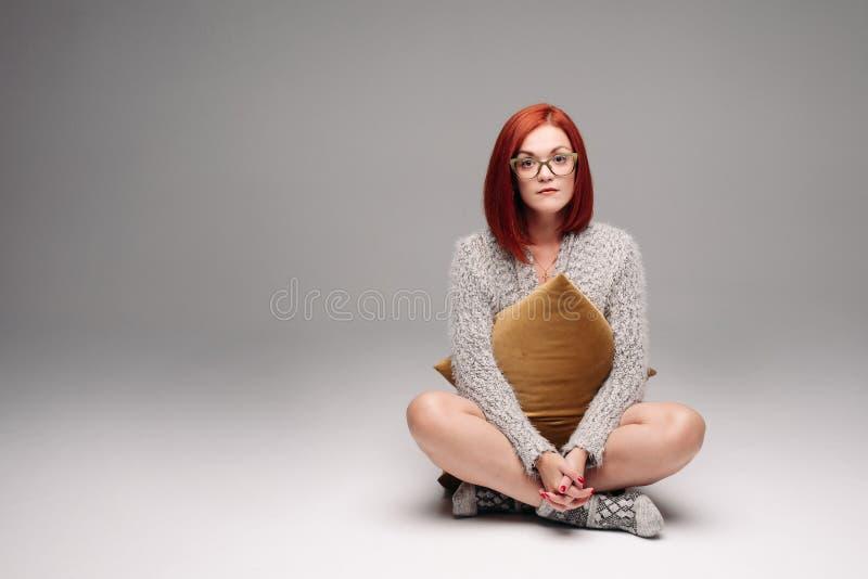 Czerwona z włosami dziewczyna w popielatym pulowerze, ciepłych skarpetach i zdjęcia stock
