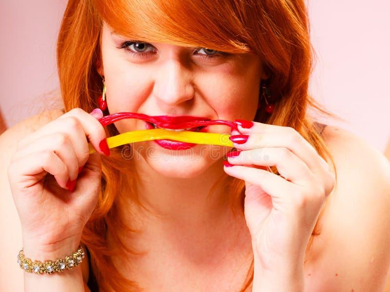 Czerwona z włosami kobieta je cukierki zdjęcia royalty free