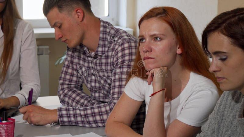 Czerwona z włosami kobieta patrzeje dokuczający podczas gdy pracujący na projekcie przy szkołą obraz royalty free