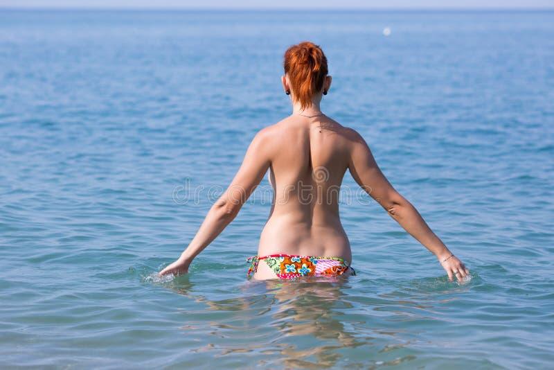Czerwona z włosami młoda kobieta w pływackich bagażnikach wchodzić do w morzu obraz royalty free